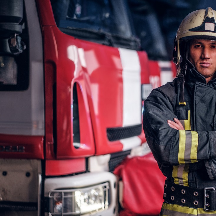 A confident fireman wearing protective uniform standing next to a fire engine in a garage of a fire department, crossed arms and looking at a camera